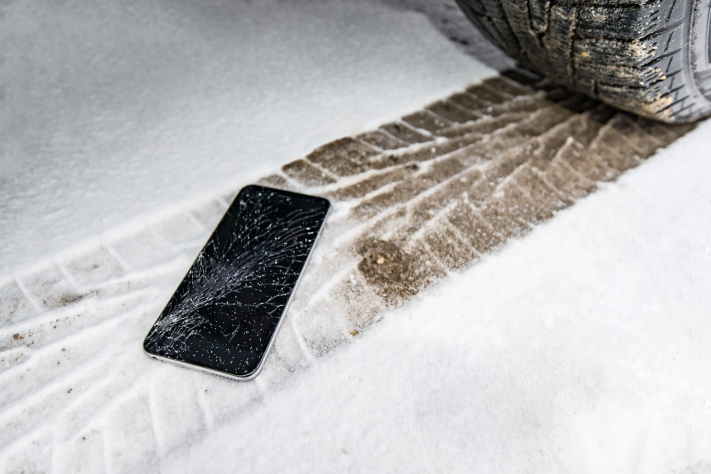 Phone with broken screen on snow in car trails